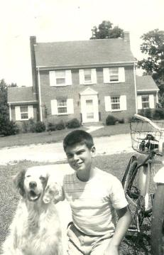 """Ray Wallace, Jr., returning from a paper route, poses with """"Joe"""", the most popular member of the Wallace family….South Crestwood Ave. in the background."""
