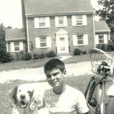 "Ray Wallace, Jr., returning from a paper route, poses with ""Joe"", the most popular member of the Wallace family….South Crestwood Ave. in the background."
